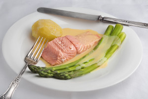 Green asparagus and poached salmon with sauce maltaise (hollandaise variation) with a potato on a white plate with old style silverware.