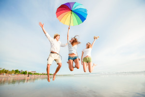 Group of happy young people having fun jumping with rainbow umbrella on the beach on bali