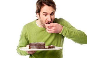 Anxious young male tasting the chocolate cake