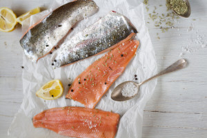 Salmon trout fillets with lemon, fennel seed and salt on baking paper