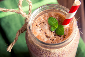 Chocolate smoothie (milkshake) with mint and straw in jar on dark wooden table